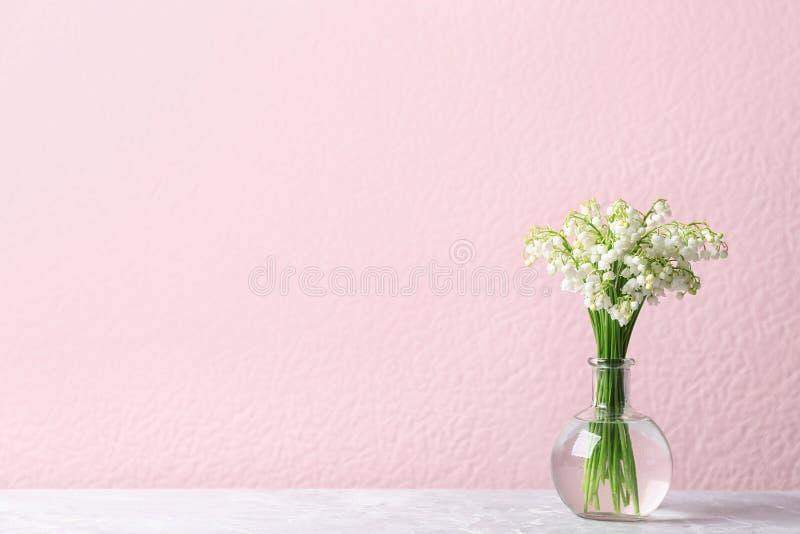 Όμορφος κρίνος της ανθοδέσμης κοιλάδων στο βάζο στον πίνακα κοντά στον τοίχο χρώματος στοκ φωτογραφίες