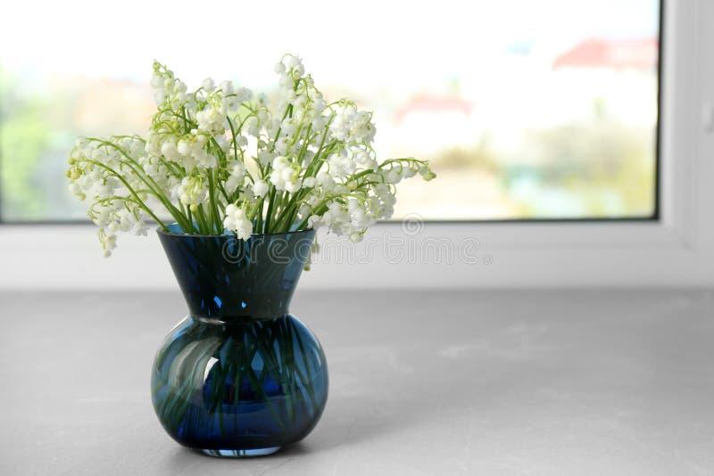 Όμορφος κρίνος της ανθοδέσμης κοιλάδων στο βάζο στο windowsill στοκ εικόνες
