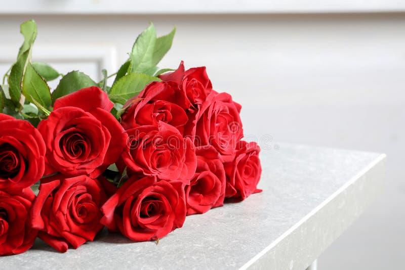 Όμορφος κόκκινος αυξήθηκε λουλούδια στον πίνακα στοκ εικόνες