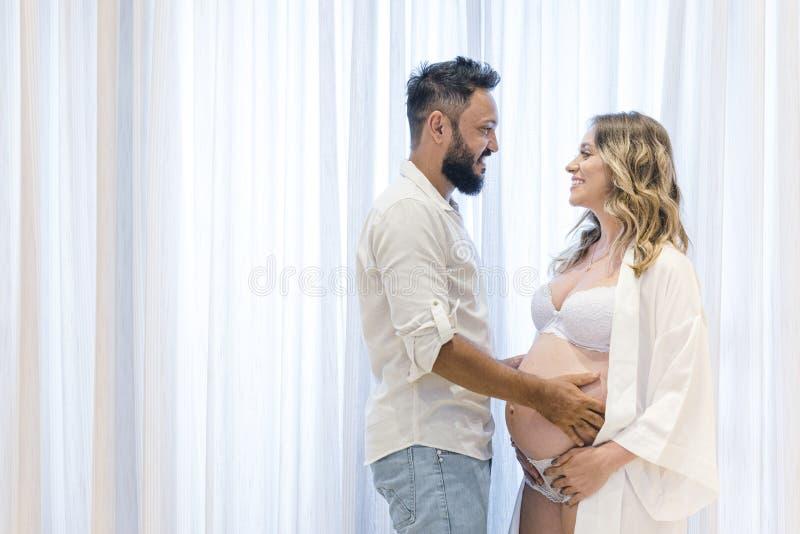 Όμορφος Λατίνος και η όμορφη έγκυος γυναίκα του, ζευγάρι που κοιτά ο ένας τον άλλο Φόντο κουρτίνας έννοια εγκυμοσύνης στοκ φωτογραφίες