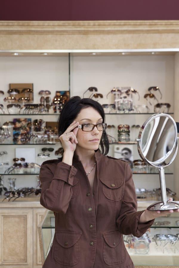 Όμορφος μέσος ενήλικος θηλυκός πελάτης που προσπαθεί στα γυαλιά εξετάζοντας τον καθρέφτη στοκ φωτογραφία
