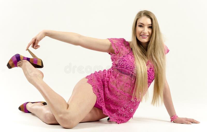 Όμορφος μακρυμάλλης ξανθός σε ένα ρόδινο φόρεμα που στέκεται την πολύβλαστη, flirty ανύψωση φουστών στοκ φωτογραφία με δικαίωμα ελεύθερης χρήσης