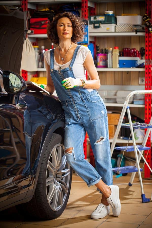 Όμορφος μηχανικός γυναικών στην μπλε επισκευή μελετών φορμών τζιν guid στοκ φωτογραφίες