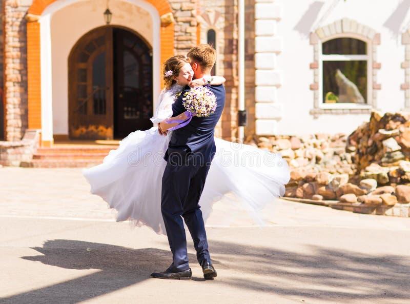 Όμορφος μοντέρνος νεόνυμφος που κρατά τη μυθική ευτυχή συναισθηματική νύφη και που έχει τη διασκέδαση υπαίθρια στοκ εικόνες