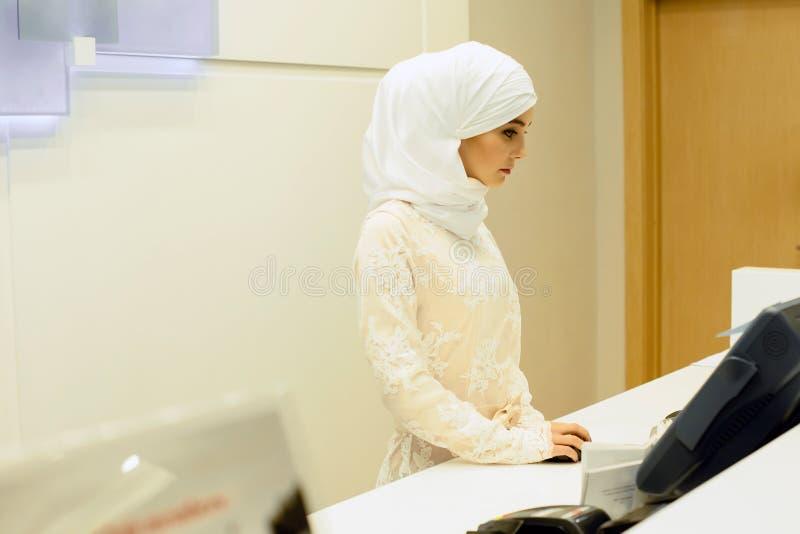 Όμορφος μουσουλμάνος, διοικητής ξενοδοχείων, που εργάζεται στην υποδοχή γραφείων στοκ εικόνα με δικαίωμα ελεύθερης χρήσης