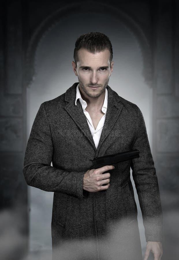 Όμορφος μυστικός πράκτορας που κρατά ένα πυροβόλο όπλο στοκ εικόνα με δικαίωμα ελεύθερης χρήσης