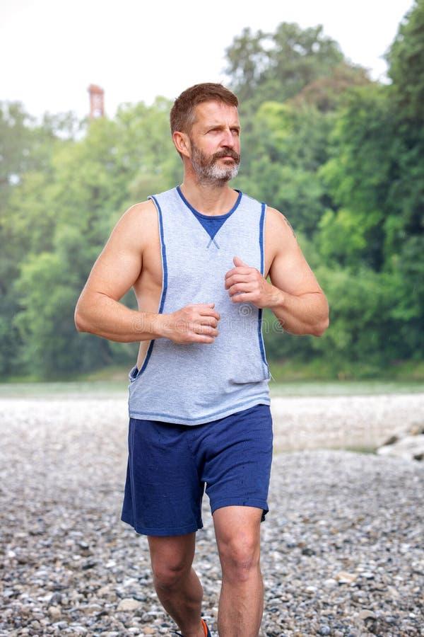 Όμορφος μυϊκός γενειοφόρος αθλητής που τρέχει υπαίθρια στοκ φωτογραφίες
