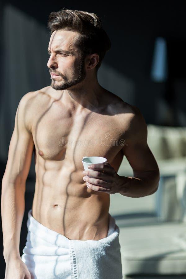 Όμορφος, μυϊκός, νεαρός άνδρας που πίνει τον καφέ πρωινού του σε ένα χ στοκ εικόνες