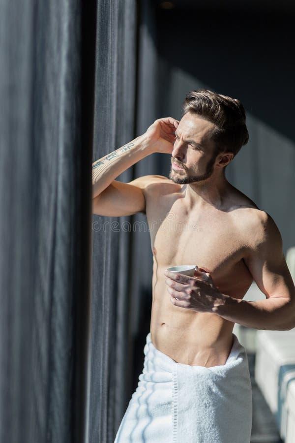 Όμορφος, μυϊκός, νεαρός άνδρας που πίνει τον καφέ πρωινού του σε ένα χ στοκ φωτογραφίες με δικαίωμα ελεύθερης χρήσης