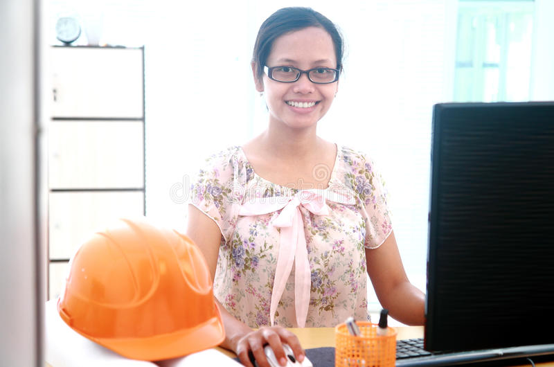 Όμορφος νέος αρχιτέκτονας γυναικών που εργάζεται στον υπολογιστή της σε offic στοκ φωτογραφία