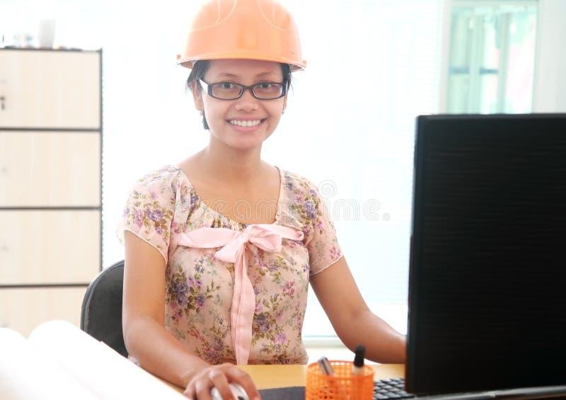 Όμορφος νέος αρχιτέκτονας γυναικών που εργάζεται στον υπολογιστή της στοκ φωτογραφίες