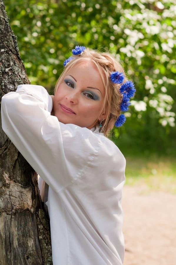 Όμορφος νέος αδύνατος αγκώνας γυναικών στο δέντρο στοκ εικόνα