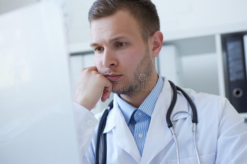 Όμορφος νέος γιατρός που χρησιμοποιεί τον υπολογιστή στο γραφείο στην κλινική στοκ φωτογραφίες