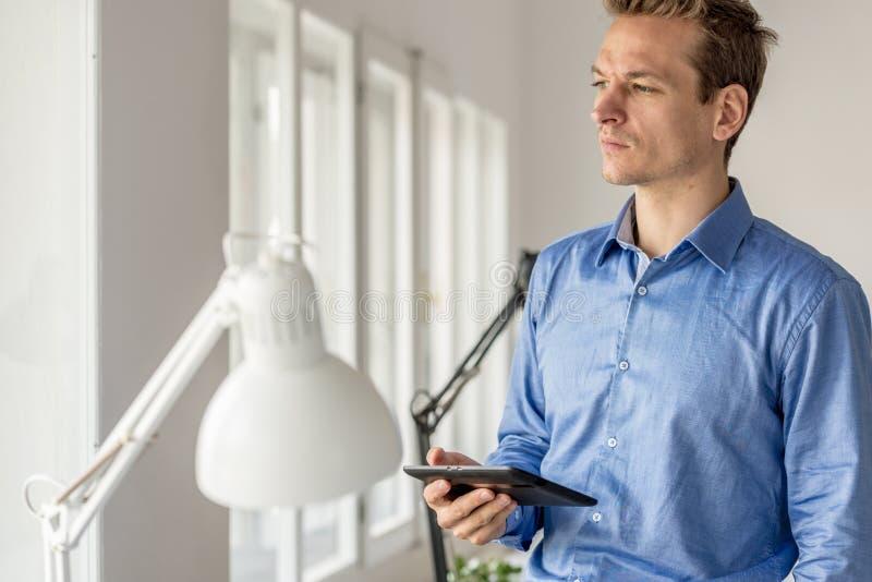 Όμορφος νέος επιχειρηματίας που υπερασπίζεται τα παράθυρα γραφείων στοκ εικόνα με δικαίωμα ελεύθερης χρήσης