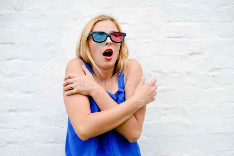 Όμορφος νέος κινηματογράφος προσοχής γυναικών με τα τρισδιάστατα γυαλιά, χέρια εκμετάλλευσης διέγερσης στοκ φωτογραφία