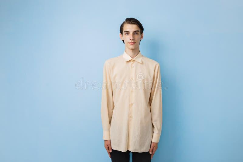 Όμορφος νέος λεπτός σκοτεινός-μαλλιαρός τύπος με τα μπλε μάτια που φορούν την κίτρινη τοποθέτηση πουκάμισων πέρα από τον μπλε τοί στοκ φωτογραφία με δικαίωμα ελεύθερης χρήσης
