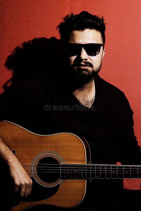 Όμορφος νέος μουσικός που παίζει την κιθάρα και το τραγούδι στοκ εικόνες