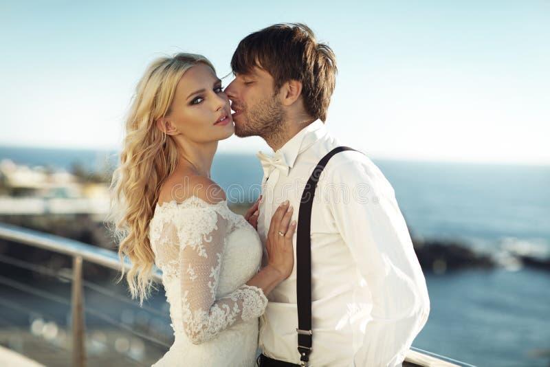 Όμορφος νέος νεόνυμφος που φιλά τη σύζυγό του στοκ φωτογραφία