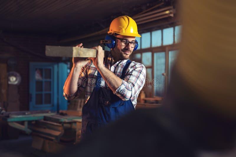Όμορφος νέος ξυλουργός στο εργαστήριο στοκ φωτογραφία