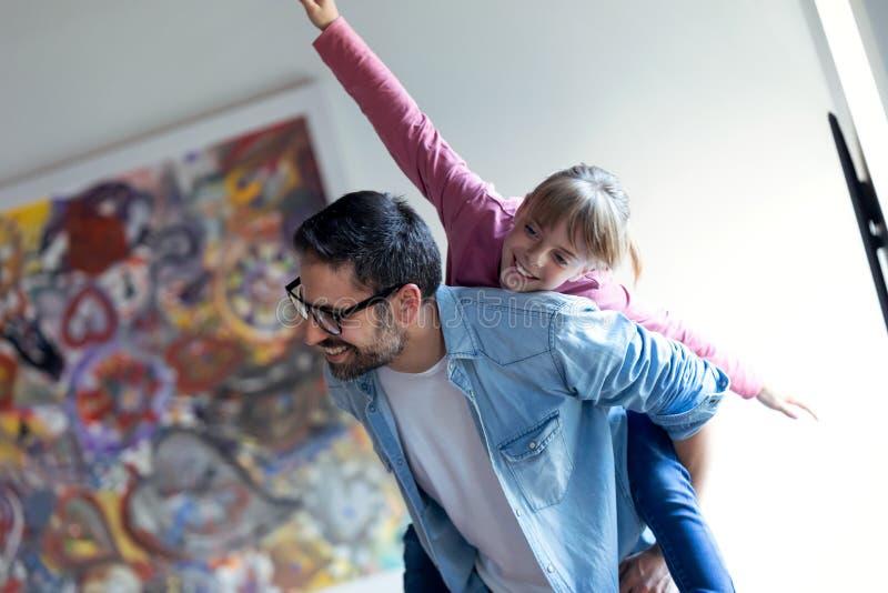 Όμορφος νέος πατέρας με την όμορφη κόρη του που απολαμβάνει το χρόνο μαζί στο σπίτι στοκ φωτογραφία με δικαίωμα ελεύθερης χρήσης