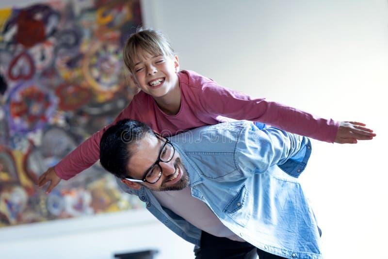 Όμορφος νέος πατέρας με την όμορφη κόρη του που απολαμβάνει το χρόνο μαζί στο σπίτι στοκ εικόνα με δικαίωμα ελεύθερης χρήσης