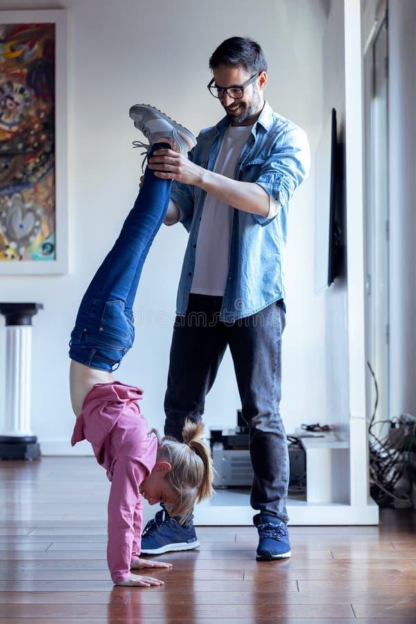 Όμορφος νέος πατέρας που βοηθά στην όμορφη κόρη να κάνει cartwheel στο σπίτι στοκ εικόνες