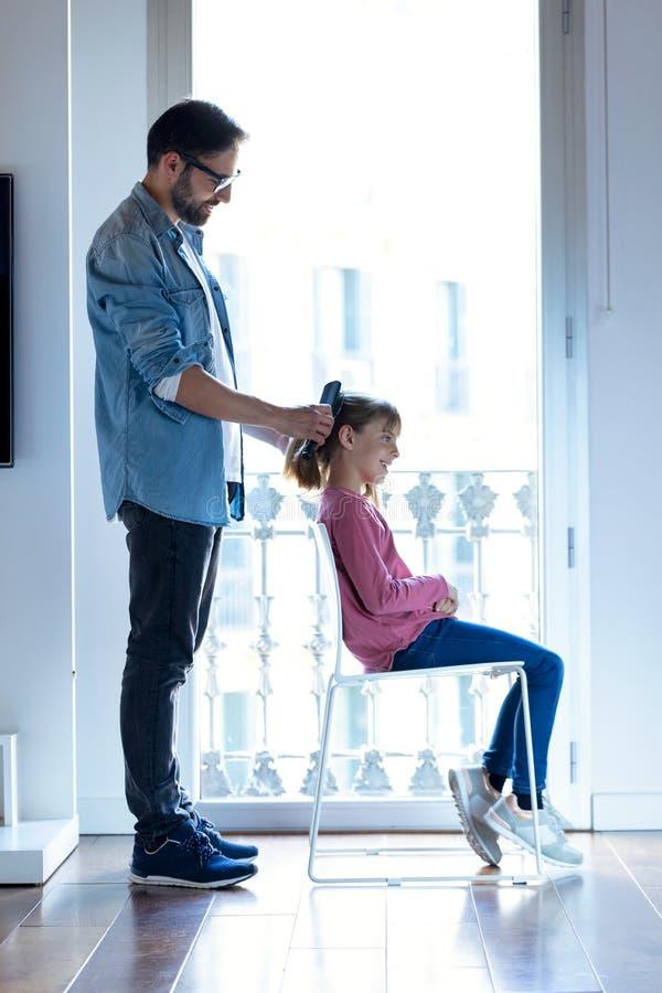 Όμορφος νέος πατέρας που κάνει ένα ponytail στην κόρη του ενώ αυτή συνεδρίαση σε μια καρέκλα στο σπίτι στοκ φωτογραφίες