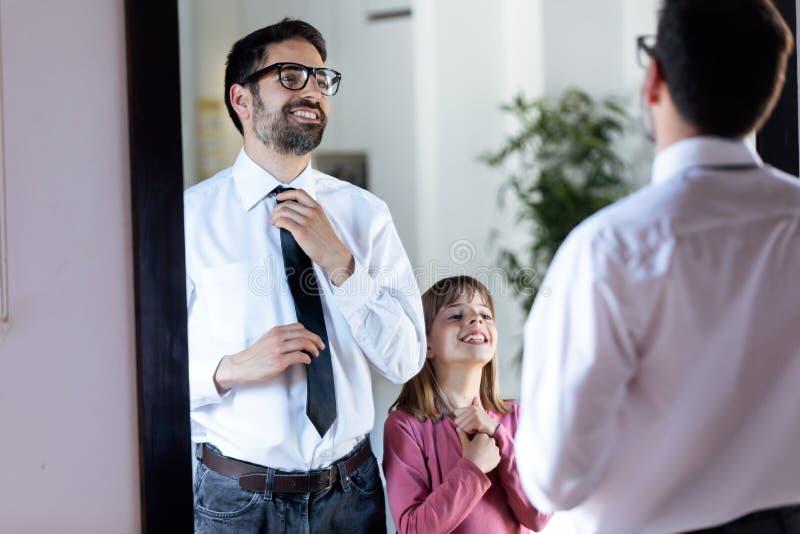 Όμορφος νέος πατέρας που καθορίζει το δεσμό του μπροστά από τον καθρέφτη και την όμορφη κόρη του που αντιγράφουν τον στο σπίτι στοκ εικόνες με δικαίωμα ελεύθερης χρήσης