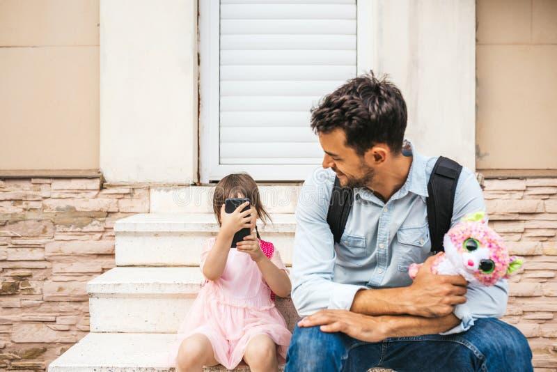 Όμορφος νέος πατέρας που ξοδεύει το χρόνο μαζί με το μαθητή κορών του μετά από τον παιδικό σταθμό Χαριτωμένη έξυπνη τηλεφωνική λή στοκ εικόνα με δικαίωμα ελεύθερης χρήσης