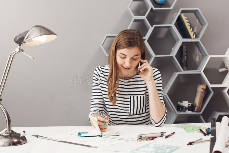 Όμορφος νέος σχεδιαστής επιχειρηματιών με τη σκοτεινή τρίχα στο ριγωτό πουκάμισο που μιλά στο τηλέφωνο με τη συζήτηση πελατών στοκ φωτογραφία