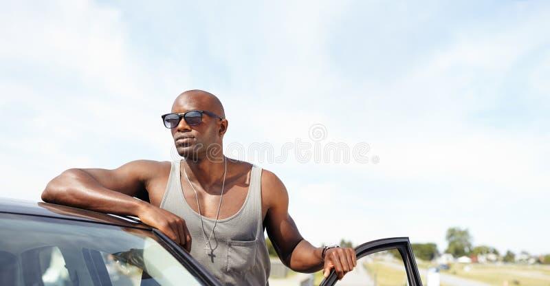 Όμορφος νέος τύπος με ένα αυτοκίνητο που κοιτάζει μακριά στοκ εικόνα με δικαίωμα ελεύθερης χρήσης