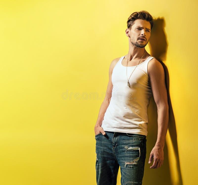 Όμορφος νέος τύπος που κλίνει στον κίτρινο τοίχο στοκ εικόνες