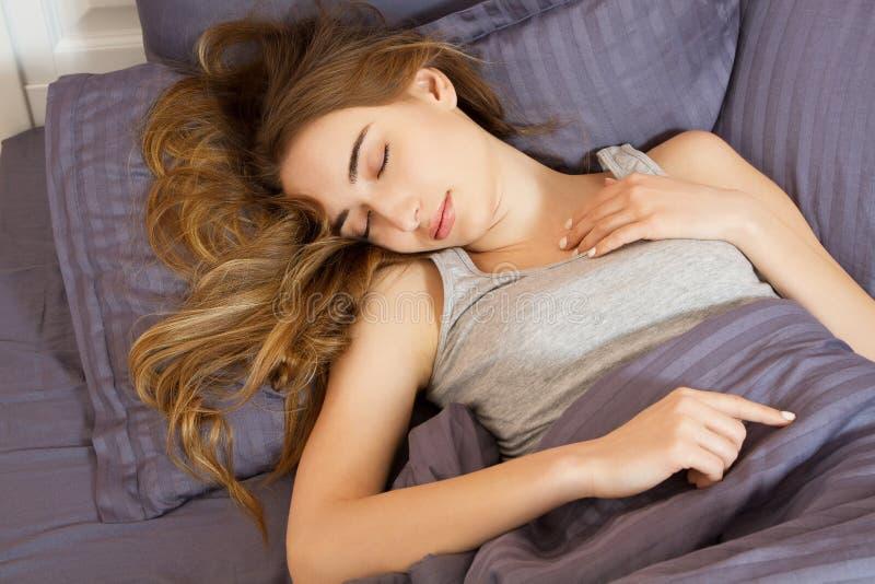 Όμορφος νέος ύπνος γυναικών σε ένα γκρίζο κρεβάτι Το κορίτσι ύπνου χαλαρώνει την έννοια στοκ εικόνα με δικαίωμα ελεύθερης χρήσης