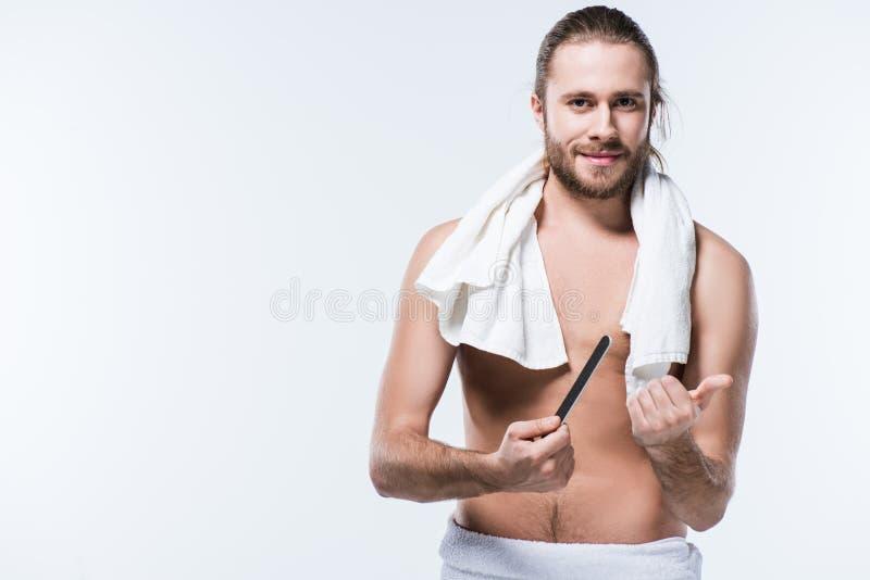 Όμορφος νεαρός άνδρας με την πετσέτα λουτρών γύρω από το αρχείο καρφιών εκμετάλλευσης λαιμών του, στοκ εικόνα
