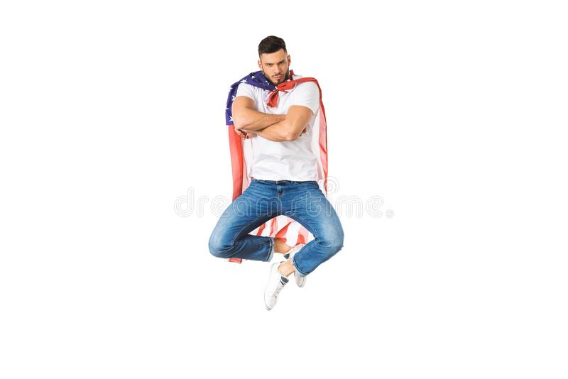 όμορφος νεαρός άνδρας με τη αμερικανική σημαία που πηδά με τα διασχισμένα όπλα και που εξετάζει τη κάμερα ελεύθερη απεικόνιση δικαιώματος