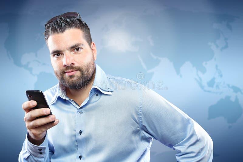 Όμορφος νεαρός άνδρας με το έξυπνο τηλέφωνο στοκ εικόνες