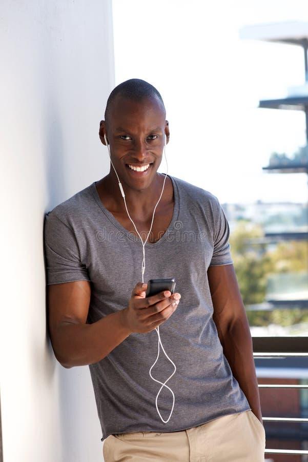 Όμορφος νεαρός άνδρας με το κινητό τηλέφωνο που ακούει τη μουσική ενάντια στον τοίχο στοκ εικόνες με δικαίωμα ελεύθερης χρήσης