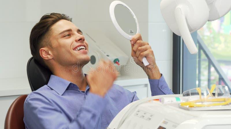Όμορφος νεαρός άνδρας που εξετάζει τα δόντια του στον καθρέφτη στην οδοντική κλινική στοκ εικόνα