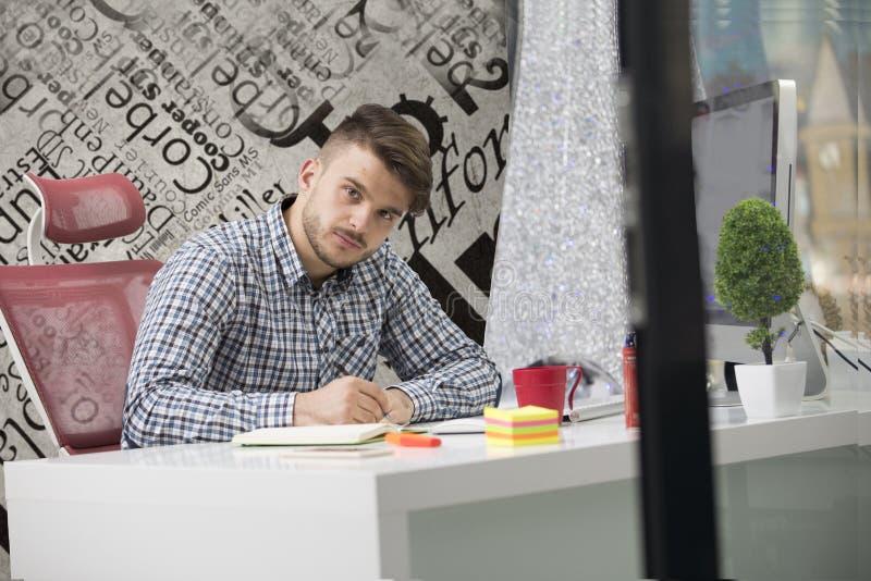 Όμορφος νεαρός άνδρας που εργάζεται με το lap-top στην αρχή στοκ φωτογραφία