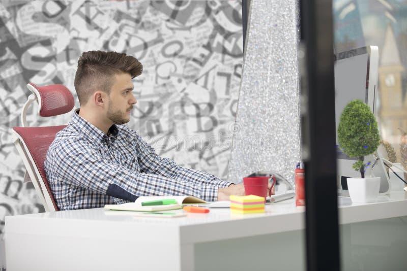 Όμορφος νεαρός άνδρας που εργάζεται με το lap-top στην αρχή στοκ φωτογραφίες με δικαίωμα ελεύθερης χρήσης