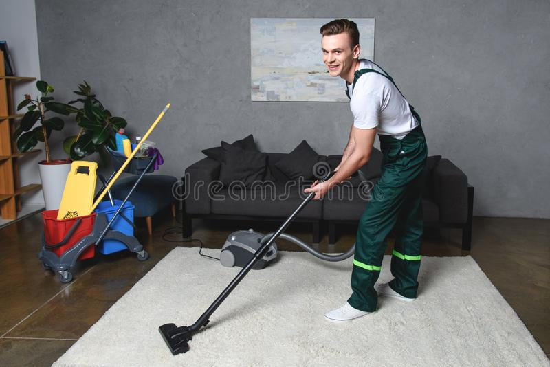 όμορφος νεαρός άνδρας που καθαρίζει τον άσπρο τάπητα με την ηλεκτρική σκούπα και το χαμόγελο στοκ εικόνες με δικαίωμα ελεύθερης χρήσης
