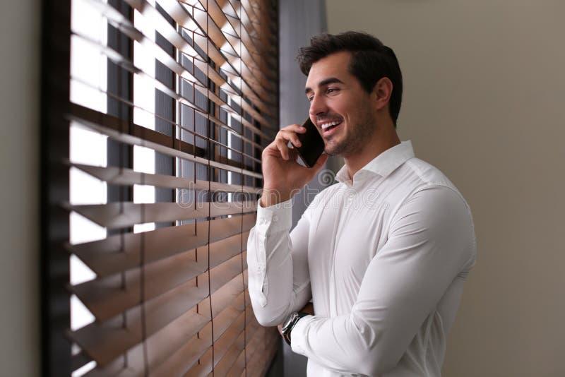 Όμορφος νεαρός άνδρας που μιλά στο smartphone πλησίον στο εσωτερικό στοκ φωτογραφία