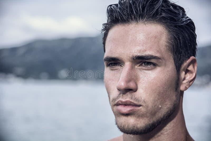 Όμορφος νεαρός άνδρας που ξεπερνά το νερό με την υγρή τρίχα στοκ φωτογραφίες