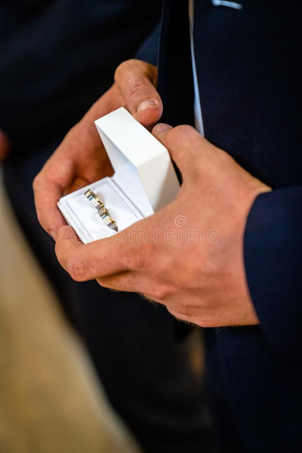 Όμορφος νεαρός άνδρας που παρουσιάζει κάτι σε ένα μικρό κιβώτιο, γαμήλια δαχτυλίδια, ένα γαμήλιο δαχτυλίδι, δαχτυλίδι αρραβώνων στοκ φωτογραφίες με δικαίωμα ελεύθερης χρήσης