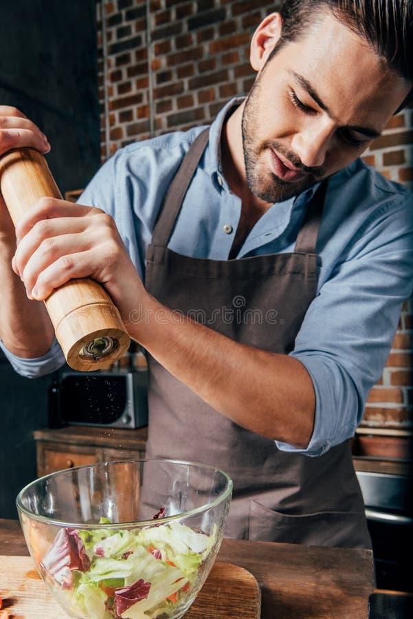 όμορφος νεαρός άνδρας που προσθέτει το πιπέρι με το μύλο στοκ φωτογραφία