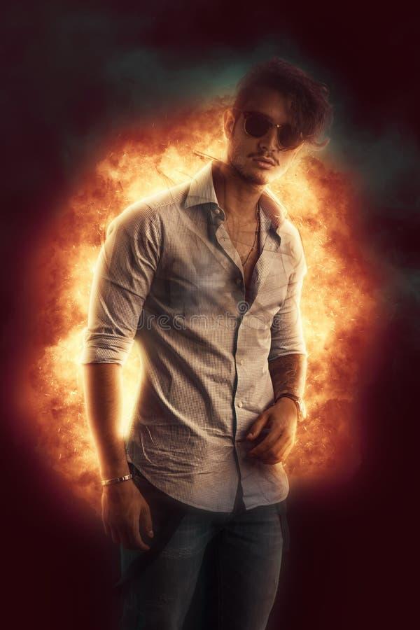 Όμορφος νεαρός άνδρας που στέκεται ενάντια στην έκρηξη φλογών στοκ φωτογραφίες