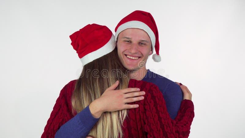Όμορφος νεαρός άνδρας που φορά το καπέλο Χριστουγέννων που αγκαλιάζει τη φίλη του στοκ φωτογραφία