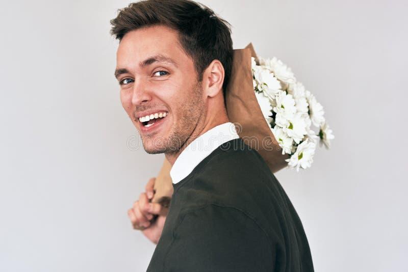 Όμορφος νεαρός άνδρας που χαμογελά και που παραδίδει μια ανθοδέσμη των άσπρων λουλουδιών Ελκυστικό αρσενικό πρότυπο με μια δέσμη  στοκ φωτογραφία με δικαίωμα ελεύθερης χρήσης