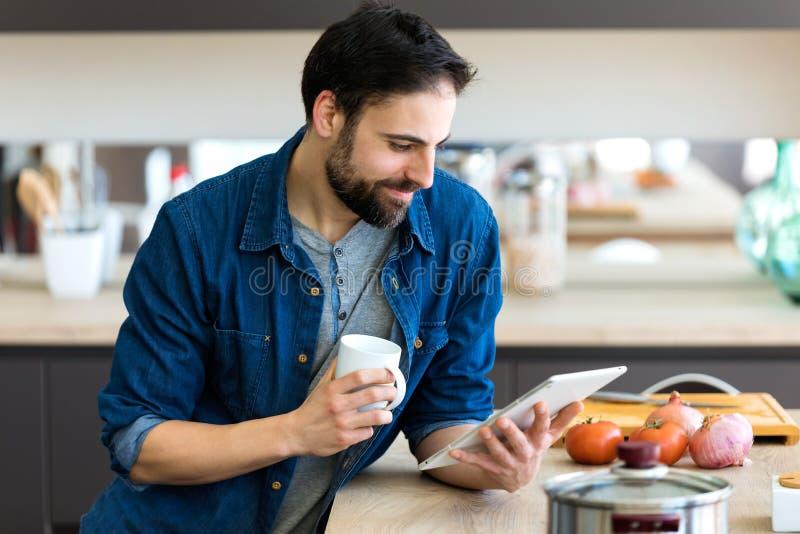 Όμορφος νεαρός άνδρας που χρησιμοποιεί την ψηφιακή ταμπλέτα του πίνον στοκ εικόνα με δικαίωμα ελεύθερης χρήσης