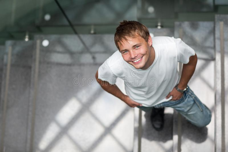 Όμορφος νεαρός άνδρας σε μια σκάλα, που ανατρέχει στοκ εικόνα με δικαίωμα ελεύθερης χρήσης